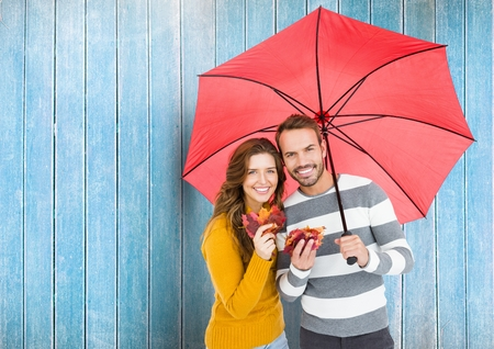 Composite image of happy couple with umbrella against blue wooden background Stock Photo