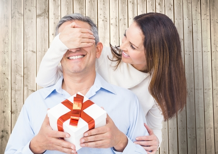 Woman covering mans eyes while gifting against wooden background Stock Photo