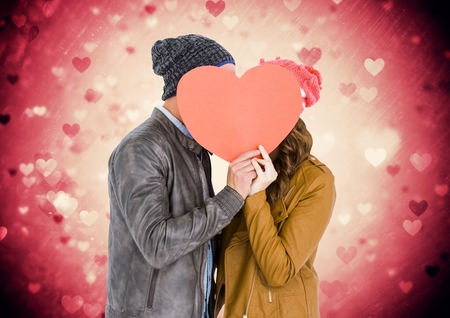 bobble: Composite image of romantic couple hiding their face behind heart Stock Photo