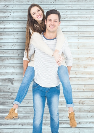 piggyback ride: Man giving piggyback ride to woman against wooden background