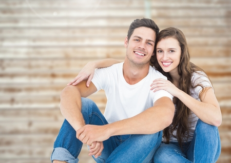 Romantic couple smiling and relaxing against wooden background Stock Photo