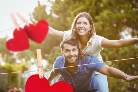Composite image of hanging red hearts and man giving a piggyback ride to woman