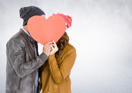 Romantic couple holding heart shape and kissing each other against white background