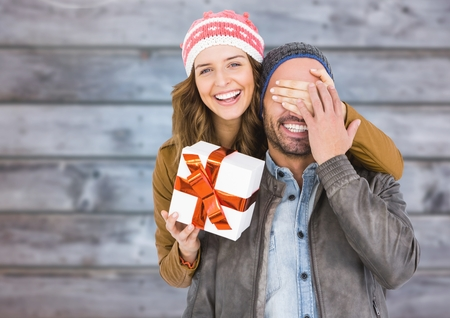 mouth smile: Woman covering mans eyes while gifting against wooden background Stock Photo