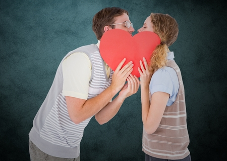 focus on foreground: Romantic couple kissing behind heart against teal background