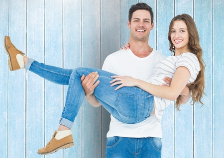 Portrait of happy man carrying his woman against blue wooden background Stock Photo