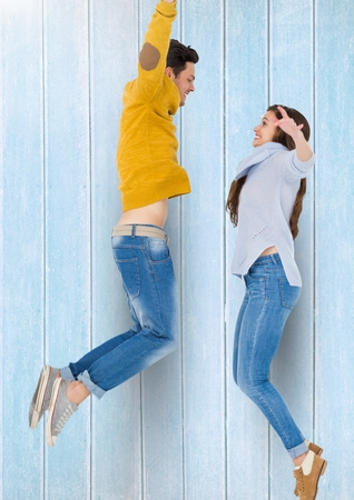 Excited couple jumping together in mid-air against wooden background