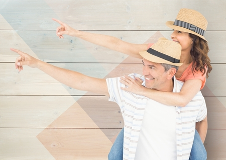 aside: Loving couple pointing aside against wooden background Stock Photo