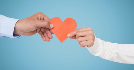 Hands of couple holding a heart against blue background Stock Photo