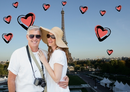 french culture: Composite image of tourist couple standing against digitally generated eiffel tower and hearts Stock Photo