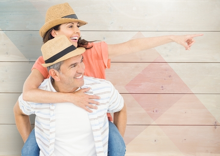 man holding transparent: Composite image of mature man giving piggy back to woman against wooden background Stock Photo