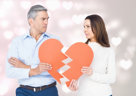 Mature couple holding a broken heart against digitally generated background Stock Photo