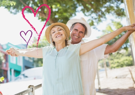 Composite image of senior couple standing with arms outstretched Stock Photo