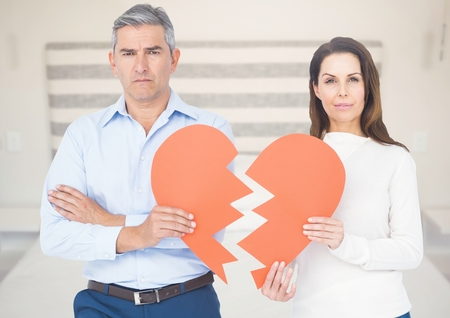 Composite image of couple holding broken heart against blur background