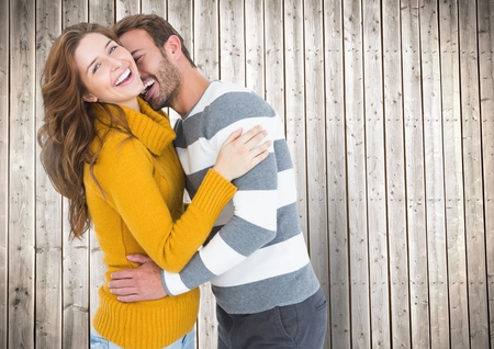 each: Romantic couple cuddling each other against wooden background