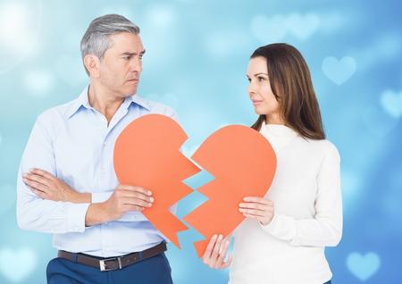 Composite image of sad couple holding broken heart