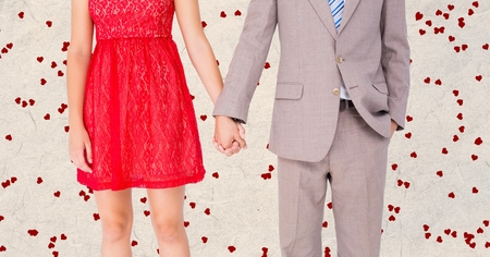midsection: Mid-section of couple holding hands against digitally generated hearts background