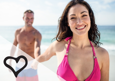 foreground focus: Happy couple holding hand at the beach with digitally generated heart