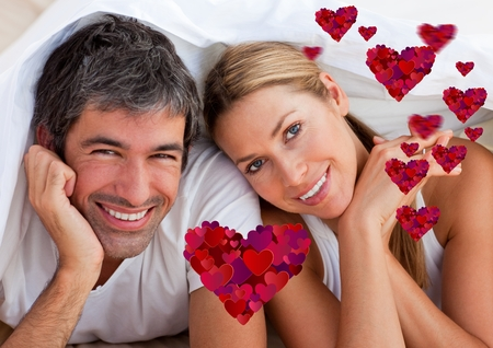 Portrait of digital composite of happy couple lying on bed at home
