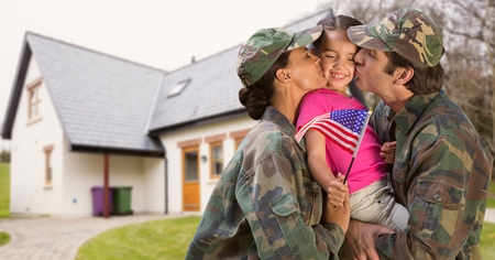 Happy parents in soldiers uniform kissing their daughter in garden
