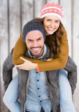 bobble: Man giving piggy back to woman against wooden plank background