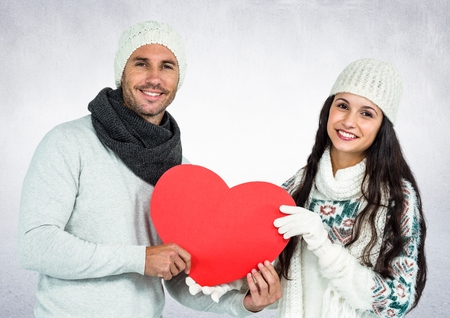 Portrait of smiling couple holding red hearts against digitally generated snowy background