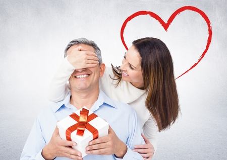 Smiling woman surprising man with a gift against digitally generated red heart Stock Photo