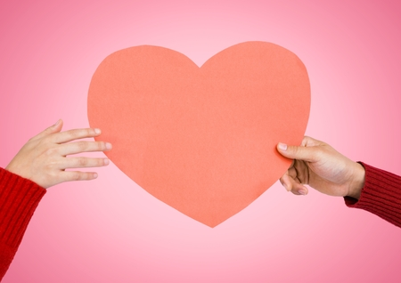 Close-up of couples hands holding heart against pink background