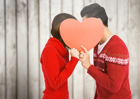Couple kissing behind heart against wooden plank background