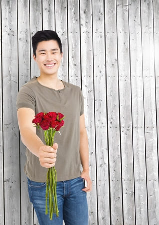 man holding transparent: Smiling man holding bunch of flowers against wooden plank background Stock Photo