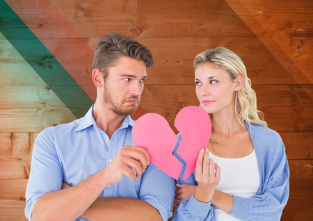 Sad couple looking each other while holding broken hearts against digital composite wooden background Stock Photo