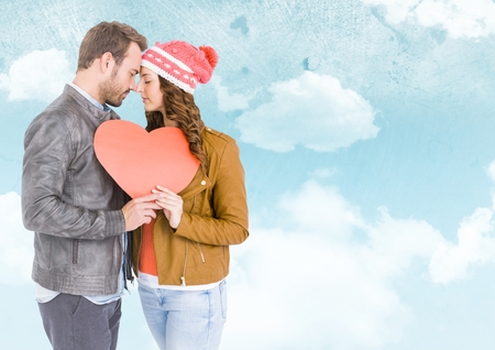 Romantic couple holding heart against digitally generated sky background Stock Photo