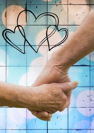 couple holding hands: Close-up of senior couple holding hands against digitally generated background