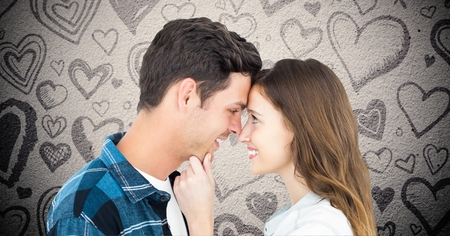Composite image of romantic couple embracing against grey background with valentines hearts Stock Photo