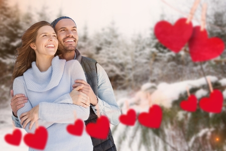 Happy couple with hearts against snow background Stock Photo