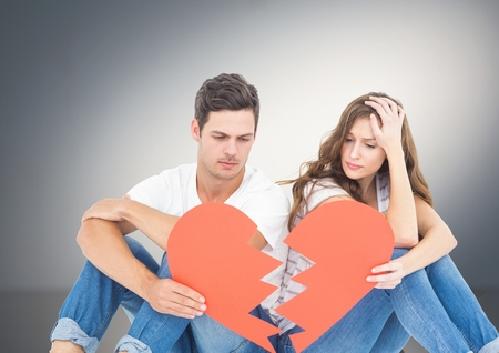 Sad couple holding broken hearts against grey background Stock Photo