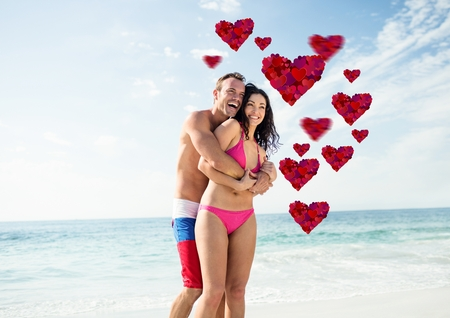 Couple embracing each other on the beach with digitally generated red heart