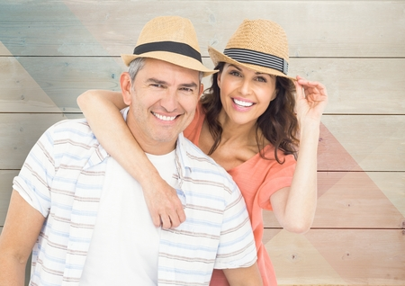 man holding transparent: Composite image of happy couple with hats against wood background