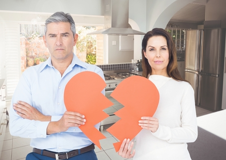 Portrait of sad couple holding broken hearts at home Stock Photo