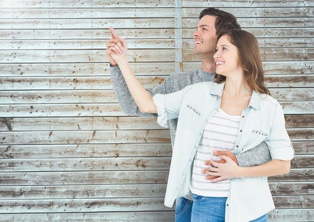 long hair boy: Happy couple pointing at distance against wooden background
