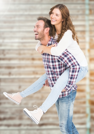 Happy man giving piggy back to woman against digital composite background