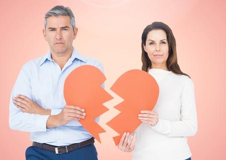 Upset couple holding broken heart against pink background