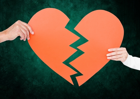 strife: Close up of couple hands holding broken heart against digital generated green background
