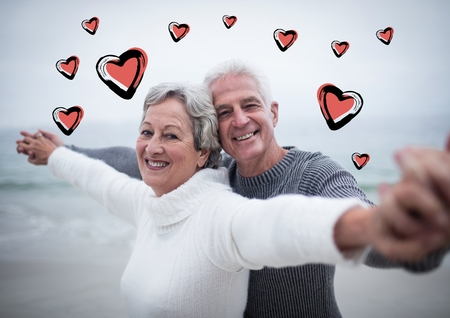 70s: Portrait of senior couple standing with arms outstretched on beach against digitally generated heart background