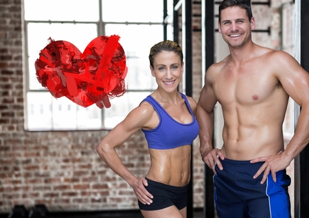 Portrait of fitness couple with digitally generated red heart Stock Photo