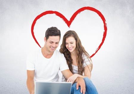 Happy couple using laptop against digitally generated red heart