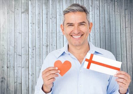 Portrait of senior man holding red heart and gift card against wooden background