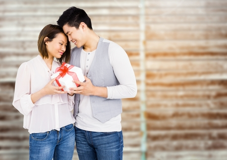 Romantic couple holding gift box against digital composite background