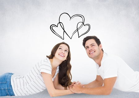 man looking out: Composite image of black hearts and thoughtful couple lying on floor against white background