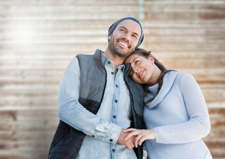 Portrait of happy couple embracing against wooden background Stock Photo
